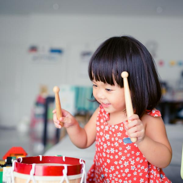Little Girl playing toy drum