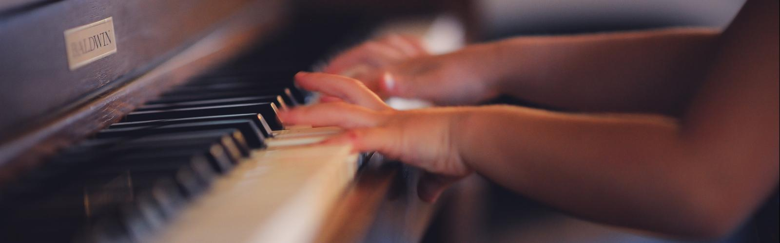 Young student's hands at piano, stock image (Unsplash)